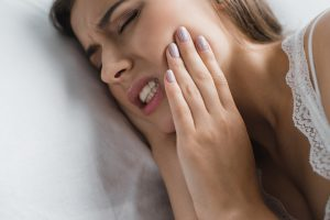young woman suffering from tooth ache and headache from grinding in sleep